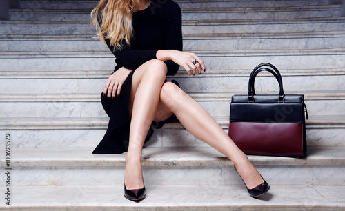 Fashion model sitting in black dress with big bag high heel shoes