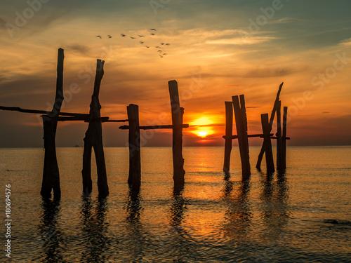 wschód słońca na plaży ze złamanym drewnianym mostem