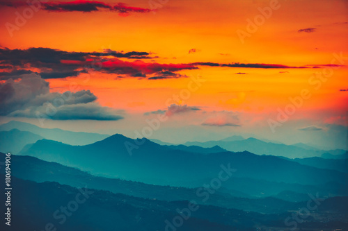 Fotobehang Groen blauw Magnificent sunset views of the mountain range with the altitude of the aircraft. Picturesque and gorgeous evening scene with bright orange sky. Color toning effect. Beauty world.