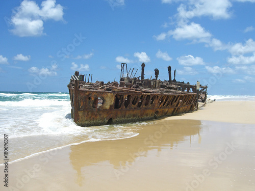 Deurstickers Schipbreuk rusty shipwreck on the beach with blue sky