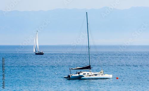 Catamaran is moored in calm sea of Adriatic sea.