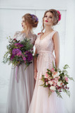 Two bride girls with hairdos with colored strands holding bouquets of flowers in their hands. - 180705700