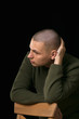 A young man is skinhead in a green military style sweater. studio.