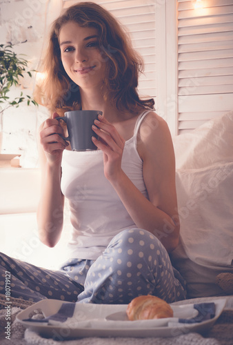 Pretty woman drinking coffee sitting on bed at home