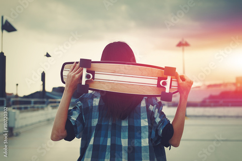 Fotobehang Skateboard Young hipster woman holding skateboard behind head in cinematic style