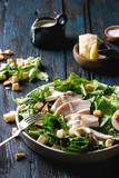 Classic Caesar salad with grilled chicken breast and half of egg in white ceramic plate. Served with fork and ingredients above over old dark blue wooden background. Rustic style - 180722143