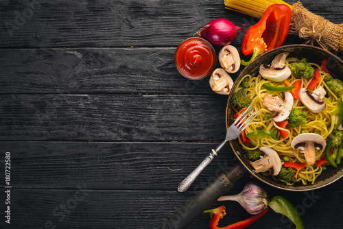 Sticker Noodles with vegetables in a frying pan. Asian Cuisine Pasta. Top view. Free space. On a wooden background.;