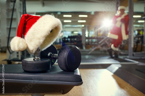 Poster Santa's hat in the gym. Concept of sports on Christmas and New Year.