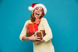 Cheerful woman in sweater and christmas hat holding gift boxes