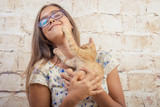girl is holding a kitten. Young beautiful girl with a red kitten in hands. Ginger cat. Girl in glasses.  - 180727763