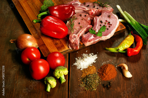 Fotobehang Steakhouse Raw steak , chops, meat with spices and vegetables on wooden table