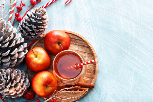 Fototapeta Seasonal and holidays concept. Winter hot tea in a glass with apples and spices on a wooden background. Selective focus, top view
