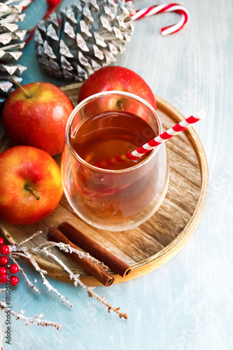 Papiers peints The Seasonal and holidays concept. Winter hot tea in a glass with apples and spices on a wooden background. Selective focus, top view