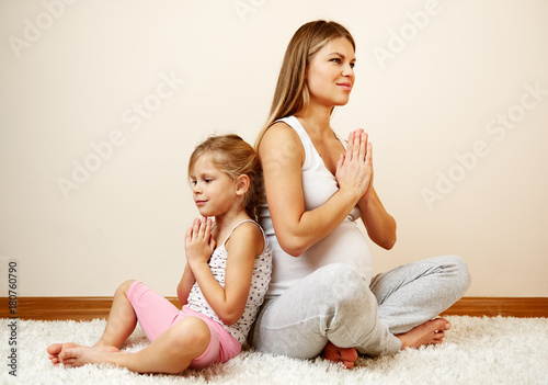 Aluminium School de yoga Pregnant woman and her little daughter meditating in yoga pose at home.
