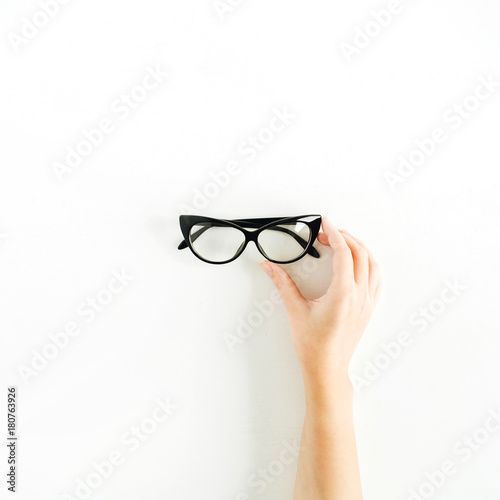 Glasses in woman hand. Minimal flat lay, top view.