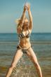 Woman wearing bikini playing with water in sea