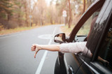 Female traveler on the road holding thumb down. Fall vacation, holidays, travel, road trip and people concept - 180765990