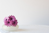Purple daisies in small glass vase on white tablecloth against white background - 180767519