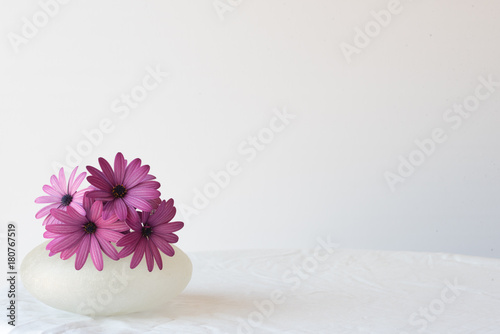 Purple daisies in small glass vase on white tablecloth against white background