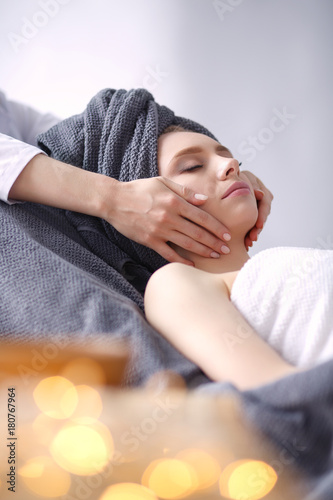 Young woman lying on a massage table,relaxing with eyes closed. Woman. Spa salon - 180767964