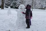 children in winter park building a snowman - 180775502