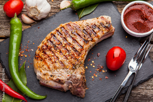 Fotobehang Steakhouse Grilled pork steak with grilled tomatoes on a dark background.