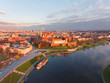 Drone aerial view at gold sunset time of royal Castle in Cracow  city center, Vistula river. Krakow, Poland