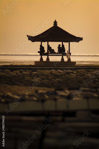 In de dag Bali Men Sitting on a Balinese Bale Gazebo During Sunset. Sanur, Bali, has a west facing view from the beach where locals and tourist gather to enjoy the sunset in one of the many Gazebos on the coastline.