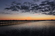 Vibrant sunset with scattered cloudscape and a fishing pier jetty
