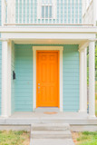Bright colored front door of remodeled urban home, tangerine orange and light turquoise baby blue - 180810975