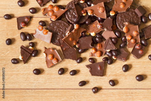 Foto op Plexiglas Kiev Dark and milk chocolate with hazelnut, round chocolate chip cookies and chocolate dragee on a wooden background