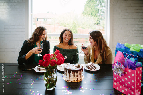 Women drinking ine and eating cake at party