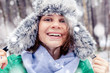 Portrait of a beautiful happy smiling young woman in a funny hat with a fur hat in a winter forest. Walks in winter
