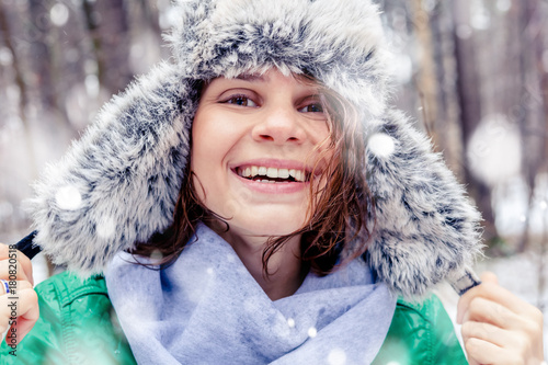 Plakát Portrait of a beautiful happy smiling young woman in a funny hat with a fur hat in a winter forest