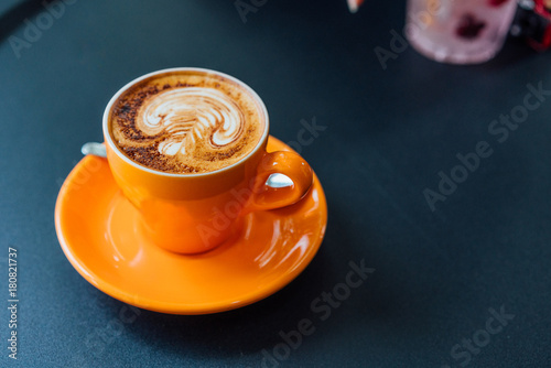 Poster coffee in orang cup on black table top