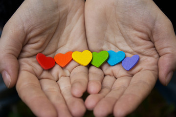 hearts of the color of the rainbow in women's hands. The LGBT Symbol