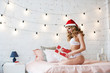 Beautiful sexy girl in santa hat with gift box in home.