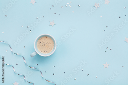 Cup of coffee on blue pastel table top view. Flat lay. Holiday morning breakfast from above.