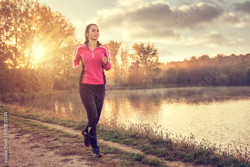 Foto op Canvas Jogging Beautiful young woman running at the lake