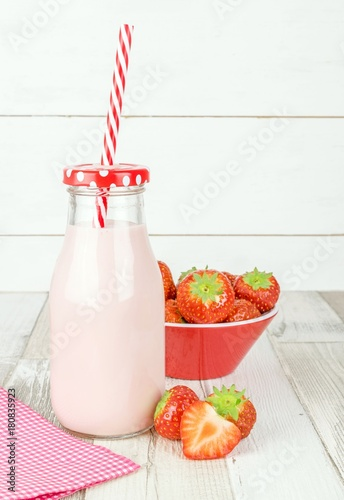 Fotobehang Milkshake A bottle of strawberry yogurt milkshakes on a wooden table with fresh fruit and copy space