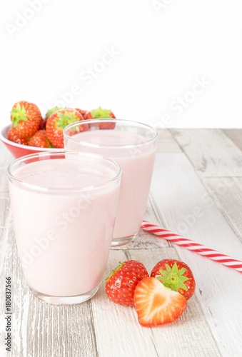 Foto op Aluminium Milkshake Two glasses of strawberry yogurt milkshakes on a wooden table with fresh fruit and copy space