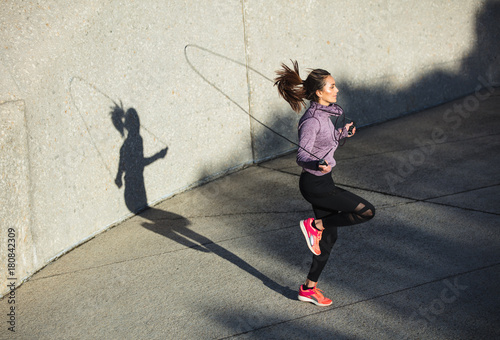 Poster Healthy woman skipping ropes outdoors
