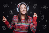 Christmas atmosphere around. Smiling inspired involved girl standing isolated in black background with the imaginary drawing and expressing peacefulness while listening to the music in the earphones - 180843168