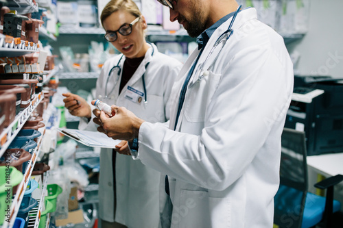 Papiers peints Pharmacie Pharmacists checking inventory at pharmacy