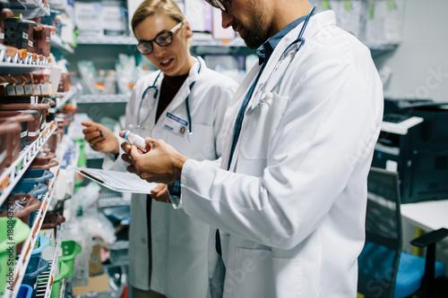 Fotobehang Apotheek Pharmacists checking inventory at pharmacy