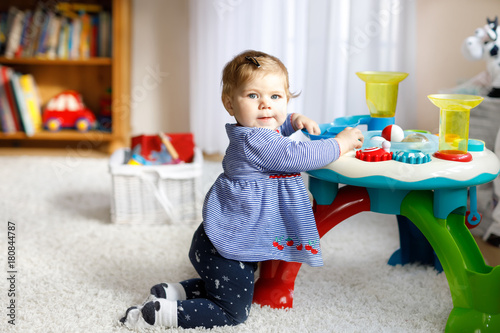 Adorable cute beautiful little baby girl playing with educational toys at home or nursery.