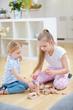 Zwei Mädchen bauen Turm mit Bausteinen