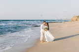 A loving couple is walking on the beach