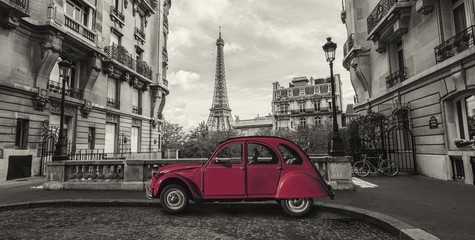 Eiffel Tower in Paris and retro red car at the  Avenue de Camoens