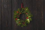 Christmas wreath decoration on rustic wood background.